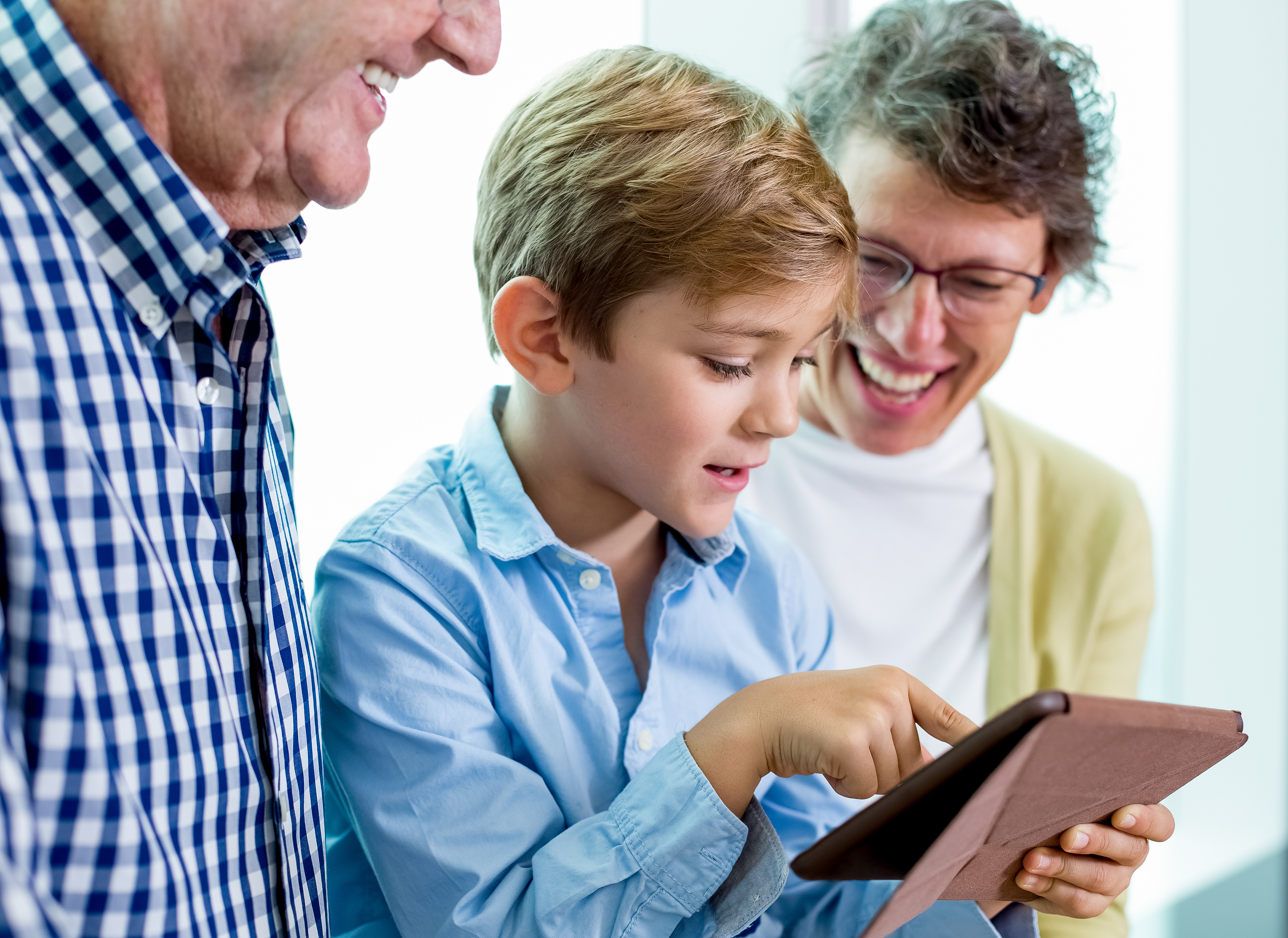 Modern child using tablet and asking grandparents. Cute boy surfing the net or looking through photos on device. Technology in life concept